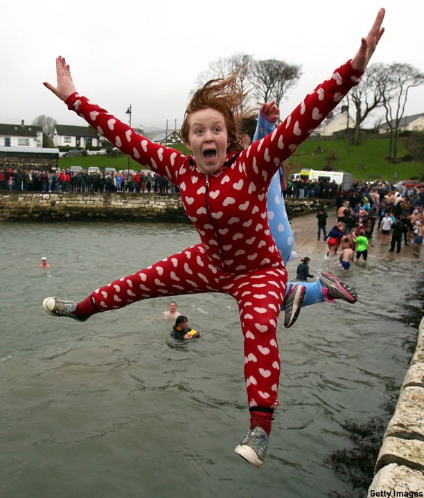 A woman jumps into Carnlough harbour, north of Belfast in Northern Ireland on January 1, 2015 for the annual New Years day charity harbour plunge. AFP PHOTO / PAUL FAITH        (Photo credit should read PAUL FAITH/AFP/Getty Images)