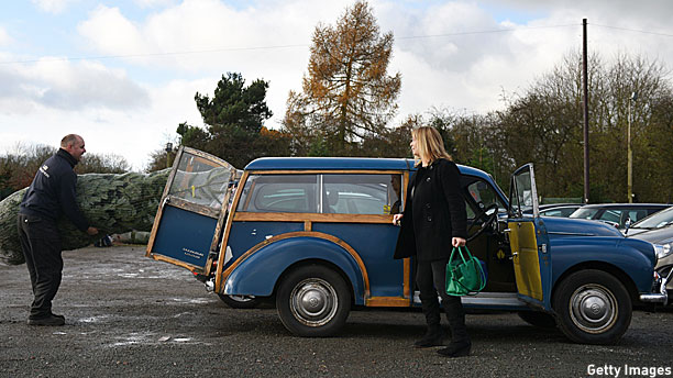 A man attempting to put his Christmas tree in a Morris Minor Traveller (Pic: Oli Scoff/Getty Images)