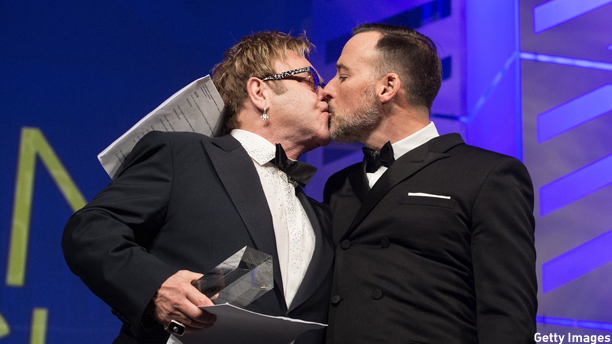 Musician Elton John and partner film maker David Furnish kiss after being presented HRC's National Equality Award at the 18th annual Human Rights Campaign (HRC) National Dinner in Washington on October 25, 2014. HRC is the largest US civil rights organization working to achieve equality for lesbian, gay, bisexual and transgender people.   AFP PHOTO/Nicholas KAMM        (Photo credit should read NICHOLAS KAMM/AFP/Getty Images)