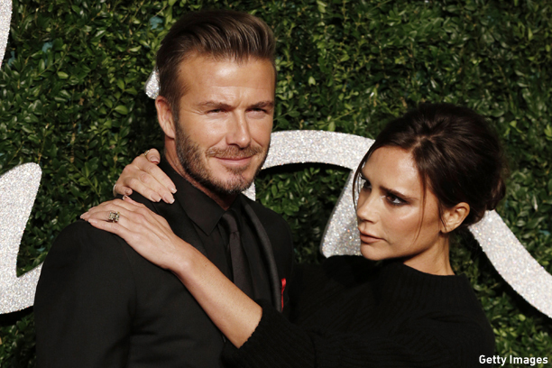 Former England football captain David Beckham and his wife British fashion designer and singer Victoria pose for pictures on the red carpet upon arrival to attend the British Fashion Awards 2014 in London on December 1, 2014. AFP PHOTO/JUSTIN TALLIS