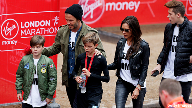 LONDON, ENGLAND - APRIL 26:  Romeo Beckham (C) receives the support of his family, brother Cruz Beckham (L), father David Beckham (2nd L), mother Victoria Beckham (2nd R) and brother Brooklyn Beckham (R) after taking part in the junior marathon during the Virgin Money London Marathon on April 26, 2015 in London, England.  (Photo by Steve Bardens/Getty Images)
