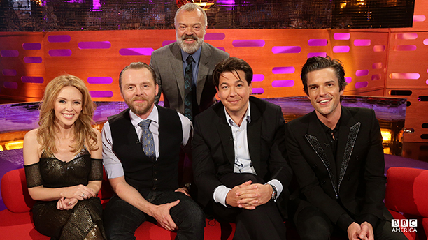 Graham Norton (back) welcomes guests (from l-r) Kylie Minogue, Simon Pegg, Michael McIntyre, and Brandon Flowers of the Killers. (Photo: BBC AMERICA)