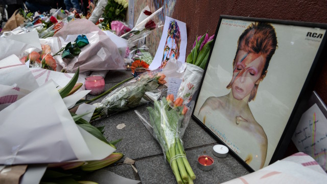 TOPSHOT – Tributes are seen beneath a mural of British singer David Bowie, following the announcement of Bowie's death, in Brixton, south London, on January 11, 2016.