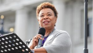 Barbara Lee, an African American woman, speaking at a podium with a microphone.