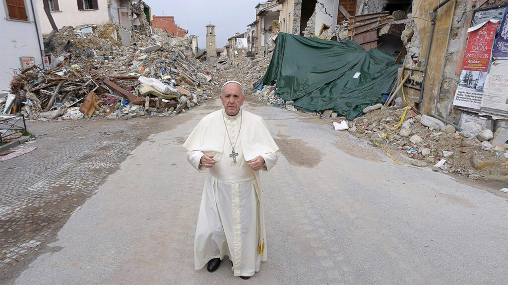 Man (Pope Francis) stands on a street with a lot of rubble in the background.