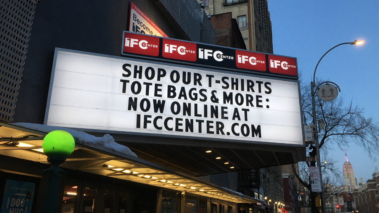 "IFC Center marquee at night with the words ""Shop our t-shirts tote bags & more: Now online at ifccenter.com"""