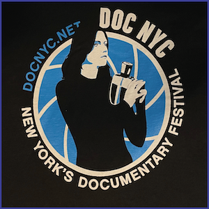 2012 DOC NYC Festival Shirt - blue and white image of a whoman with dark hair holding a handheld camera within a blue circle with text DOC NYC New York's Documentary Festival DOCNYC.NET around the circle