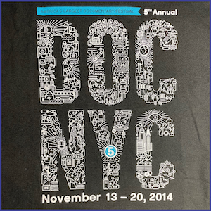2014 DOC NYC Festival shirt - words DOC NYC shaped out of doodled images into letters, the words America's Largest Documentary Festival on a blue banner and the words 5th Annual November 13-20, 2014 in white letters. Black shirt.