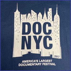 2017 DOC NYC Festival Shirt - White Ink image of city skyline with words DOC NYC and 2017 within the image. Words America's Largest Documentary Festival in white ink under the skyline image. Dark Blue Shirt.