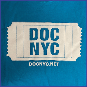 Bright blue shirt with white ink, text in large white ticket icon says DOC NYC and underneath ticket icon says DOCNYC.NET