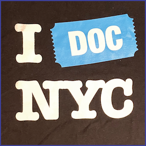 Black shirt with white letter and phrase I DOC NYC, DOC in a bright blue ticket icon